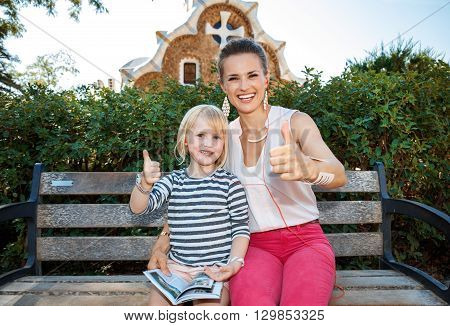 Happy Mother And Child Istening Audioguide And Showing Thumbs Up