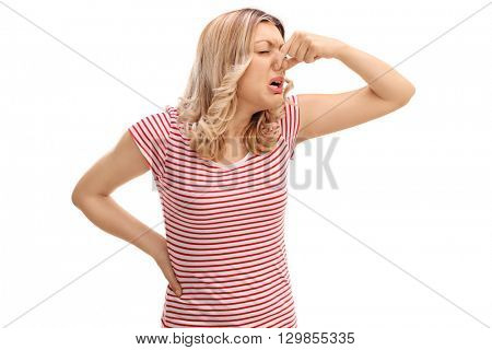 Disgusted woman closing her nose and smelling something bad isolated on white background