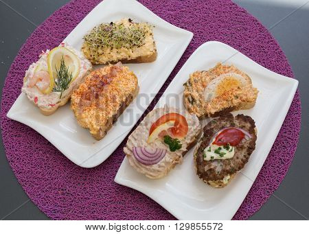 Selection of Open Sandwiches in Austria. Toppings including tuna fish minced meat and egg can be seen.