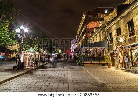 MONTREAL CANADA - 17TH MAY 2015: A view of buildings in Old Town Montreal at night showing the blur of people.