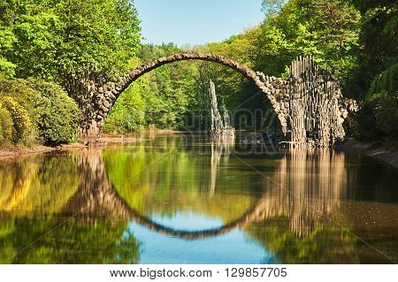 Amazing place in Germany - Rakotzbrucke also known as Devils Bridge in Kromlau. Reflection of the bridge in the water create a full circle.