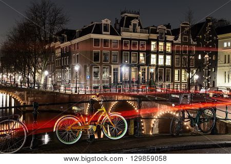 AMSTERDAM NETHERLANDS - 17TH FEBRUARY 2016: A view of bridges buildings and bikes at the Leidsegracht and Keizersgracht canal intersection in Amsterdam at night. The trail from traffic can be seen.