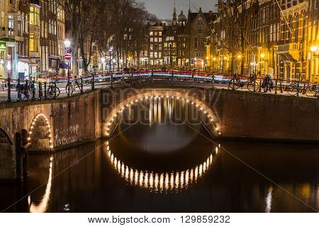 A view of the bridges at the Leidsegracht and Keizersgracht canals intersection in Amsterdam at dusk. Bikes and buildings can be seen. The trail of traffic can be seen on a bridge.