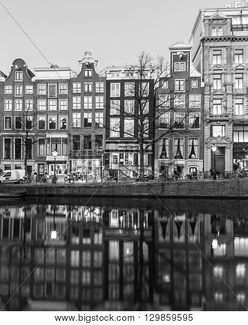 AMSTERDAM NETHERLANDS - 16TH FEBRUARY 2016: A view of buildings and shops along the Amsterdam Canals. Reflections can be seen in the water.