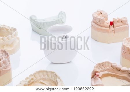Teeth Molds With Dental Floss On A Bright White Table