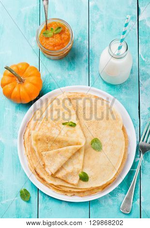 Thin crepes or pancakes with fresh pumpkin confiture, jam and bottle of milk on a rustic wooden background. Top view