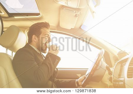 Toned picture of handsome businessman eating junk food while driving to work. Freelance man hurrying in morning to do many things.