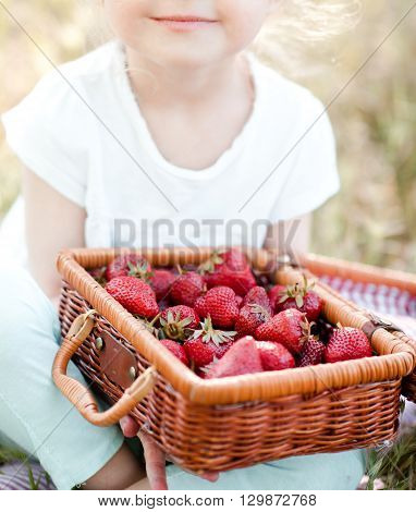 Smiling baby girl 3-4 year old holding basket with strawberries outdoors. Healthy eating. Summer season.