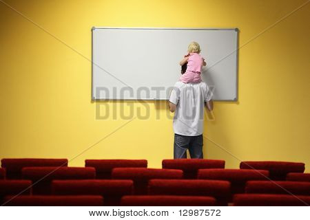little girl is sitting on father's neck and drawing on a board. chair in out of focus.