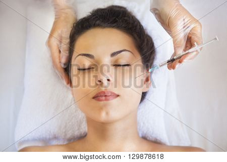 Young pretty woman getting cosmetic injection in the face like a part of the clinic treatment. Medicine healthcare and beauty concept