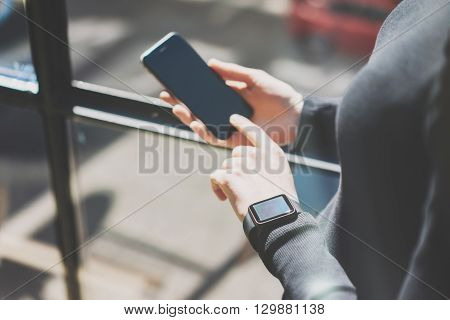 Picture Woman Working Modern Studio, Wearing Generic Design Smart Watch Hand.Female Finger Touching Screen Mobile Phone.Manage Work Process. Horizontal. Burred background. Film effects.