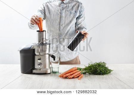 Unrecognizable Man Puts Carrots Inside Metallic Professional Juicer With Empty Glass To Make Tasty J