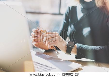 Photo Woman Working Modern Office.Girl Wearing Generic Design Smart Watch.Female Hands holding pencil. Account Manager Work Process at Wood Table.Horizontal mockup.Burred Background. Film effect.