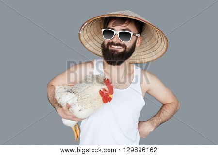 Young crazy man holding a cock and wearing sunglasses and chinese hat. Crazy vacation and holiday concept