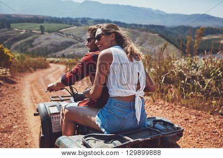 Young Happy Couple Cruising On A Quad Vehicle