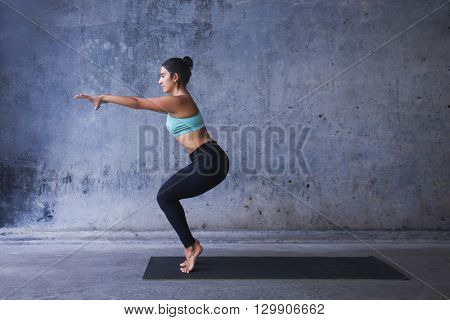 Young woman practicing yoga. Chair pose on tip toes.