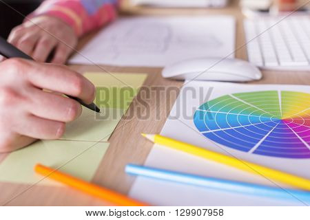 Side view of man's hand making notes on stickers placed on wooden desktop with keyboard colorful diagram pencils and other items