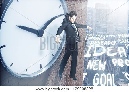 Time management concept with businessman hanging on clock arrow abstract business related words over city . 3D Rendering
