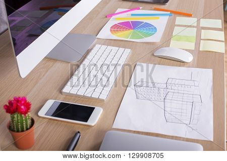 Creative designer desktop with blank phone screen construction sketch computer monitor and keyboard cactus colorful diagram and other items. Side view Mock up