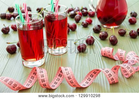 Left 2 glasses of juice with straws, scattered cherries, jar of cherry juice, in front centimeter on light green background. Cherries, cherry juice and centimeter. Horizontal.