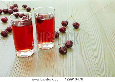 Left two glasses of cherry juice around scattered cherries, right empty space for text on light green background.  2 cherry juices and empty space. Horizontal. Close. Daylight.