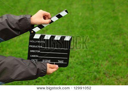 Cinema clapper board in hands of boy in jacket on field with green grass