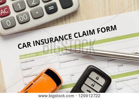 Car insurance claim form with car toy car key and calculator lay down on wooden desk concept