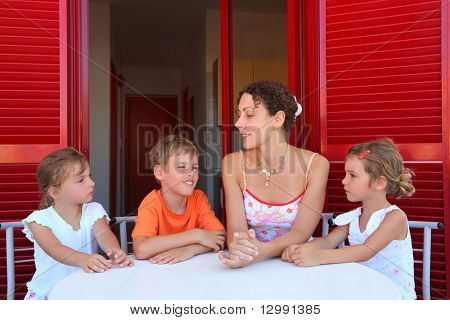 Three children and mother sit on  verandah  round table near doors and speak