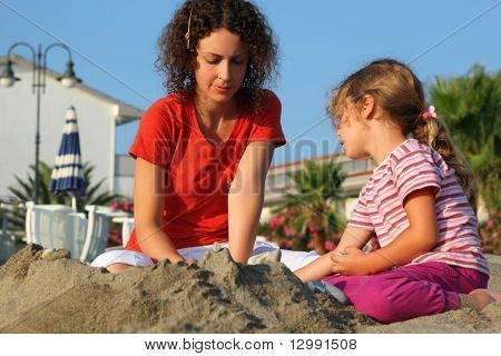 Mother with daughter sit on  beach in  day-time and play on sand