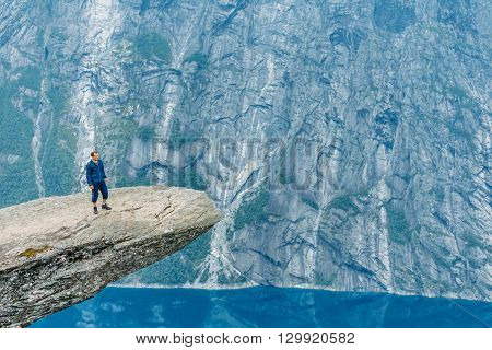 Young Man Standing On Rock In The Mountains Of Norway. Natural Attractions Of Trolltunga - Troll Tongue.