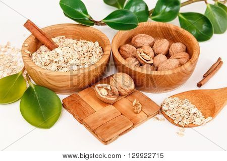 There are with Walnuts and Rolled Oats in the Wooden Plates with Sticks of Sinnamon,Wooden Support,Spoon,Green Leaves,Healthy Fresh Organic Food on the White Background