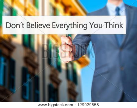 Don't Believe Everything You Think - Businessman Hand Holding Sign