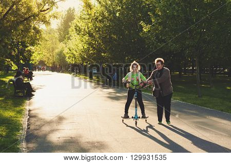 Bucharest, ROMANIA - April 22 2016: People in Izvor Park. Grandmother teaching her neice how to ride a scooter. BUCHAREST -April 22 2016