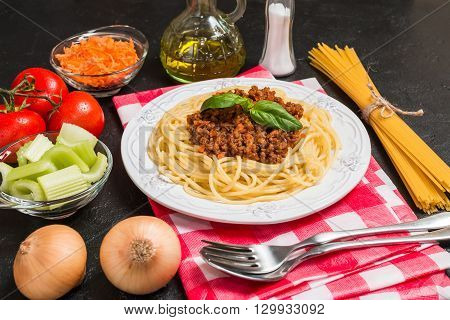 Spaghetti bologneseon white plate with ingredients on black background