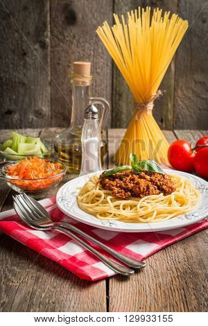 Spaghetti bologneseon white plate with ingredients on wooden background