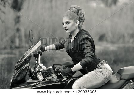 Black and white photo. Professional biker girl, fast rider, sitting on black, fast, modern motorbike, motorcycle, bike. Sexy biker girl with creative, fashionable hairstyle, leather, black jacket riding ahead.