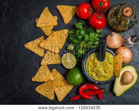 Bowl of delicious homemade Guacamole with nachos next to fresh ingredients on black background, top view