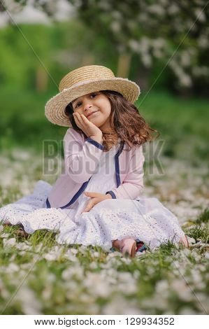 cute smiling dressy baby girl on the walk in blooming cherry garden in spring. Cozy rural scene happy childhood concept