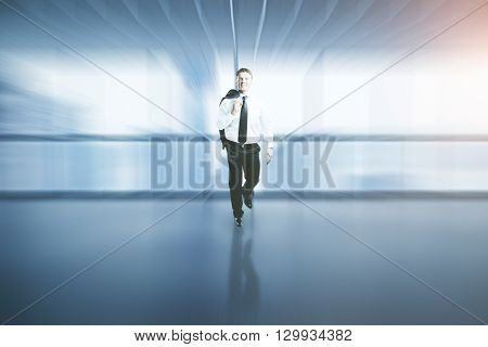 Happy successful businessman walking in blurry interior