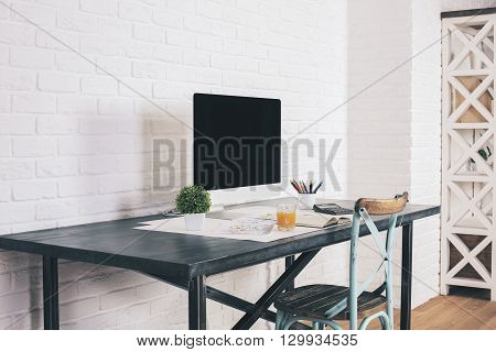 Sideview of designer desk with blank computer screen and antique chair next to it on white brick wall background. Mock up