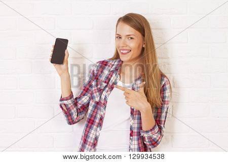 Pretty caucasian woman pointing at black smartphone in hand and smiling. White brick wall background. Mock up