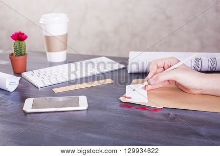 Side view of woman's hand writing on paper placed on wooden desktop with smart phone coffee cup computer keyboard cactus and other items. Mock up