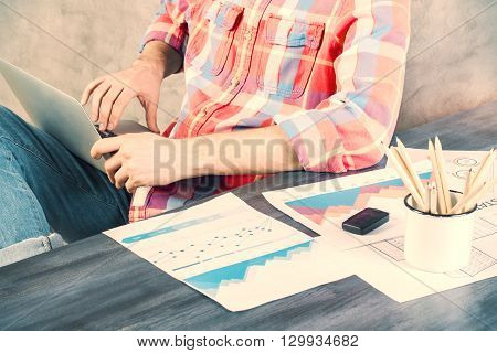 Business charts and graphs on wooden office desk with caucasian male using laptop next to it