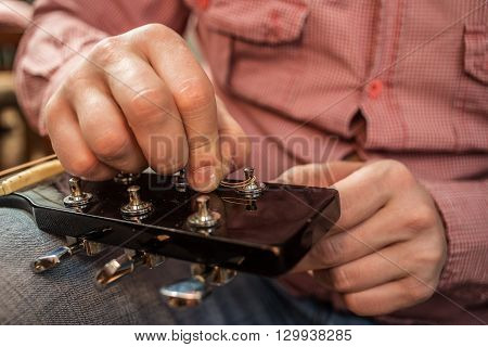 a man in a plaid shirt inserts new guitar strings to the acoustic guitar
