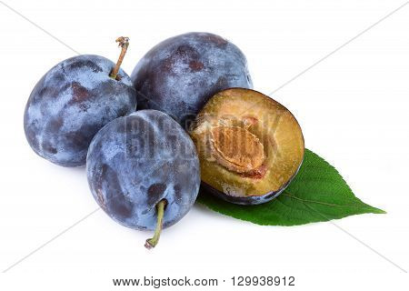 Organic plums fruit with leaves on white background. Closeup.