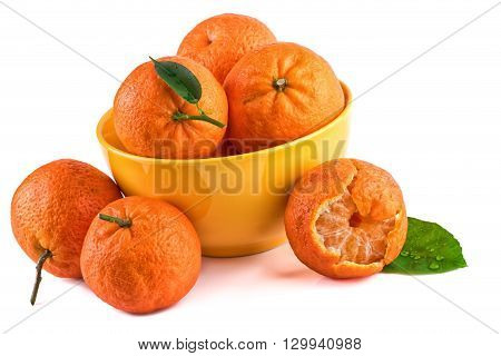 Tangerines mandarins in yellow cup isolated on white. Closeup.
