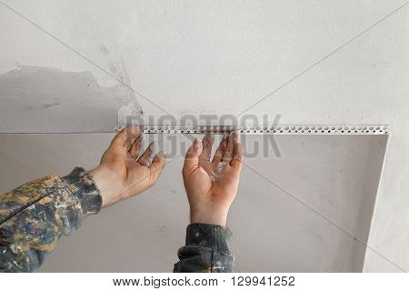 Worker Install Batten At Ceiling And Wall