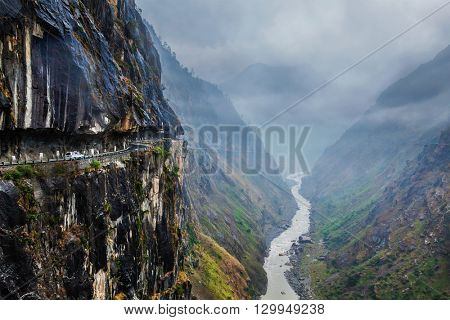 Car on dangerous road in Himalayas mountains in gorge above precipice