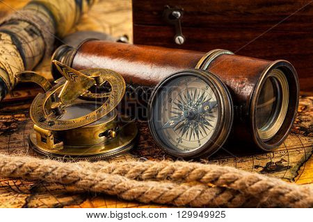 Travel geography navigation concept background - old vintage retro compass with sundial, spyglass and rope on ancient world map