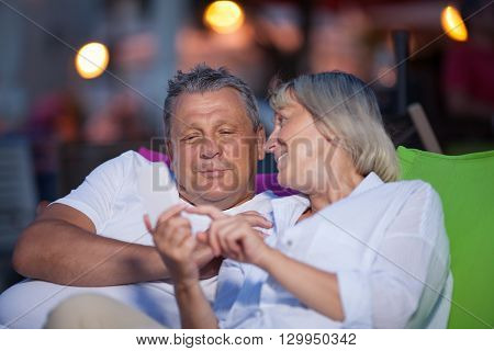 Loving middle-aged couple having an intimate chat sitting close together smiling and gesturing as they spend quality time together